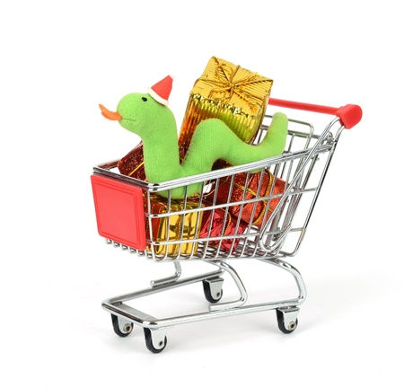 mart: Shopping cart fill with Christmas Decorations background and Cute Christmas snake Stock Photo
