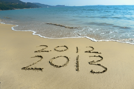 2012 and 2013 written in sand on beach photo