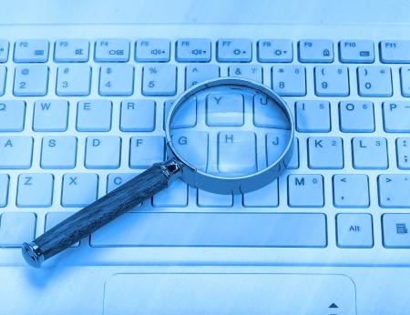 virus informatico: Ordenador portátil con una lupa