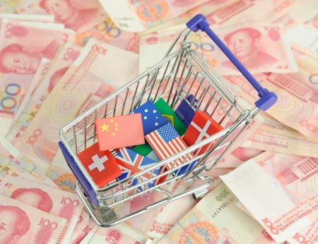 renminbi: shopping cart with national flag on a lot of Renminbi on white background