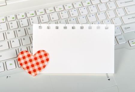 small red hearts and sticky note on Laptop keyboard photo