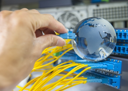 optic fiber: globe with network cables and servers in a technology data center Stock Photo
