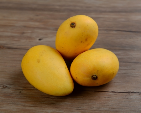 three mango in brown wicker basket isolated closeup photo