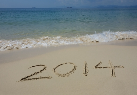 Year 2014 hand written on the white sand in front of the sea