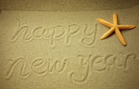 happy new year written in the sand photo