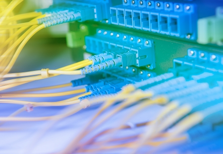 networking cables: Panel of Fiber network switch with some yellow network cables Stock Photo