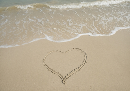 handwritten heart on sand photo