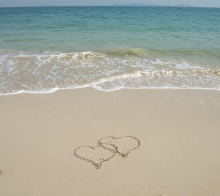 Deux coeurs dessinés dans le sable à la plage