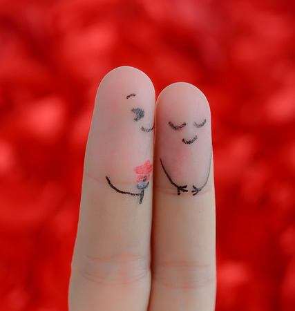 Painted finger smiley on red valentine concept. photo