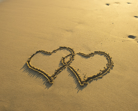 Two hearts drawn in sand at the beach photo