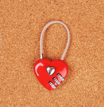 conundrum: heart shape lock locked up with wood background Stock Photo