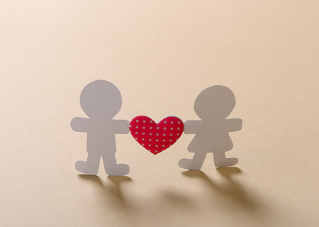 Silhouettes of men, women and heart cut out of paper on a wooden background photo