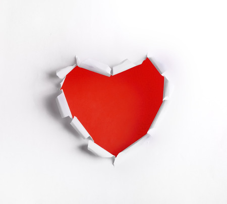 Heart shaped hole in white paper with red blank space photo