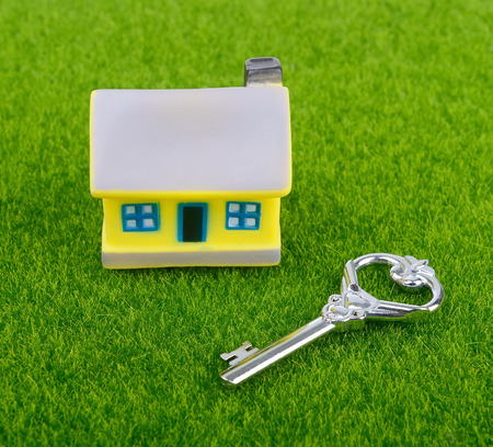 key and house on grass background photo