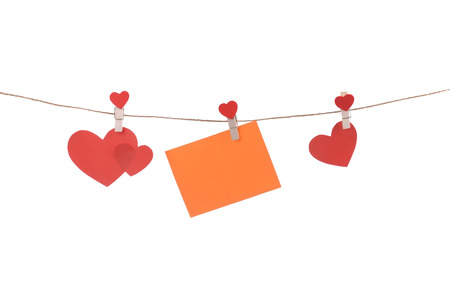 Cut out paper hearts fixed on a rope with clothespins photo