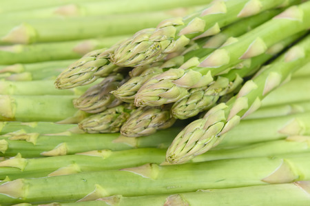 fresh green asparagus sprouts laying on bamboo background photo