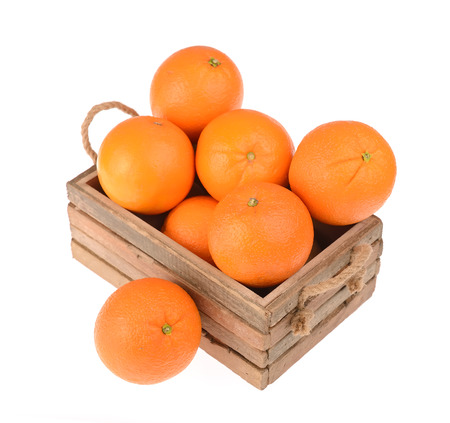 Ripe tasty tangerines with leaves in wooden box photo
