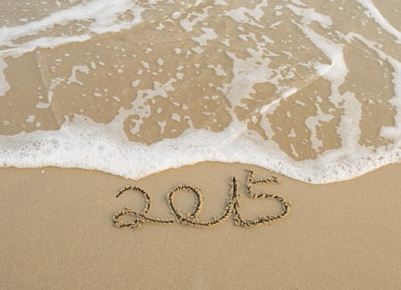 Year 2015 hand written on the white sand in front of the sea photo