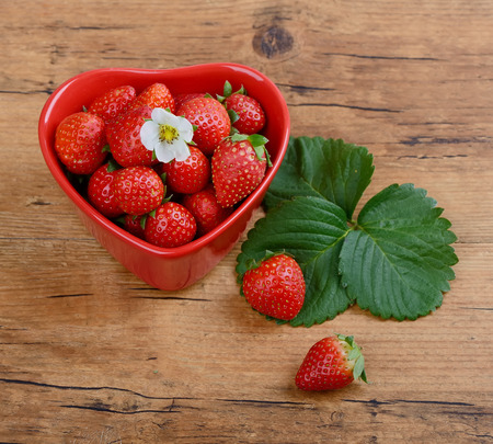 Strawberries in red heart shape bowl photo