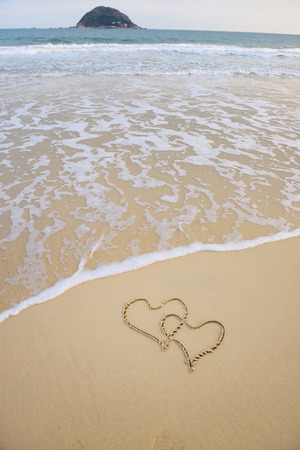 estival: two hearts drawn in beach in sunset