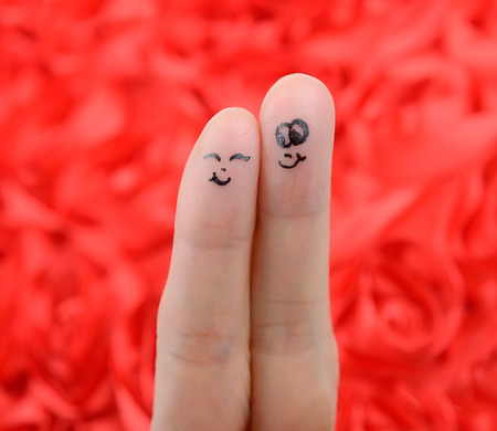 happy couple in love with painted smiley and hugging photo