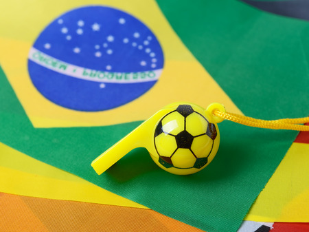 football shape whistle on brazil flag background. photo