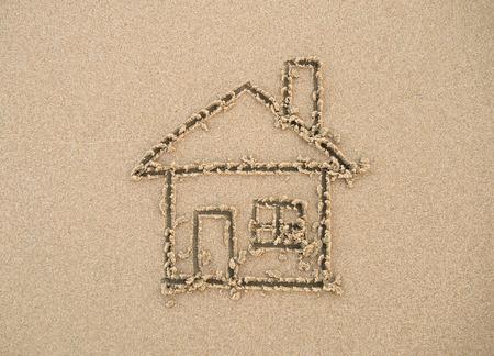 Huis geschilderd op strandzand Stockfoto