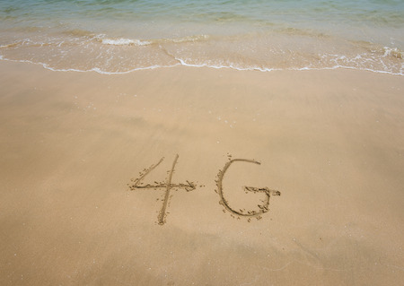 orthographic symbol: the words of 4G written on the sand at beach side