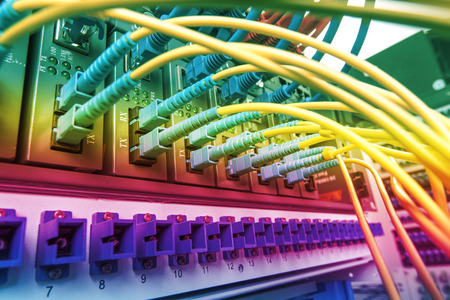 Fiber Optic cables connected to an optic port Stock Photo