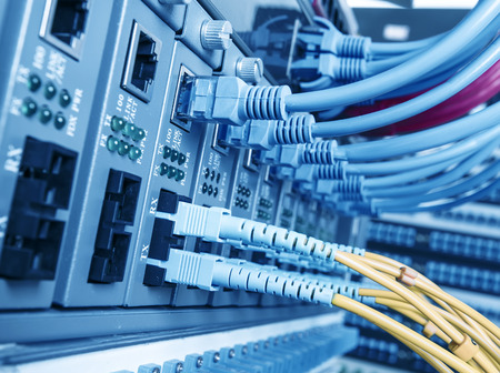 networking cables: Fiber Optic cables connected to an optic port= Stock Photo