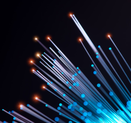 light beams: optical fibres dynamic flying from deep on technology background Stock Photo