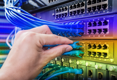 man connecting network cable to switch