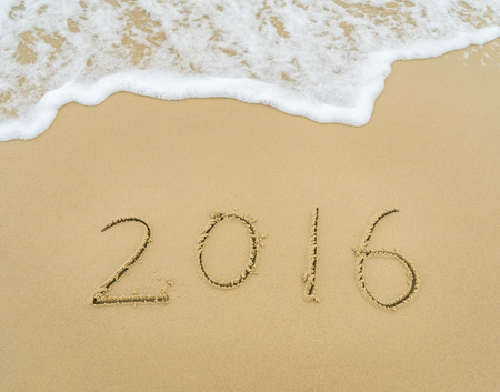 in the sand: Year 2016 written on the white sand in front of the sea Stock Photo