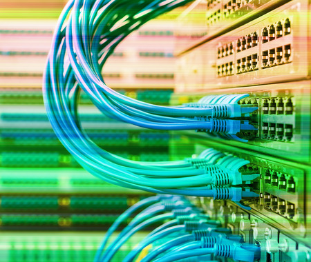 cabling: network cables and hub closeup with fiber optical background