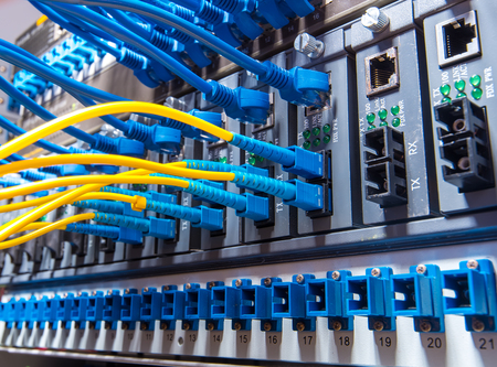 computer cable: Fiber Optic cables connected to an optic ports and Network cables connected to ports Stock Photo