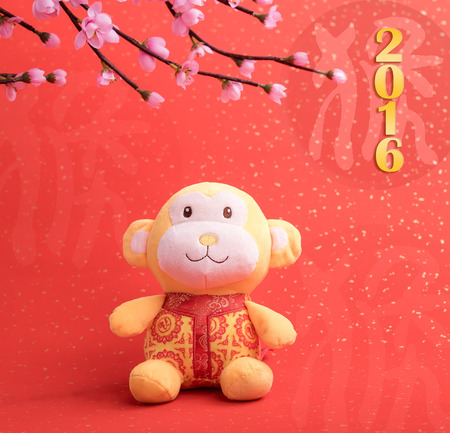 figuration: Chinese lunar new year ornaments toy of monkey on festive background Stock Photo