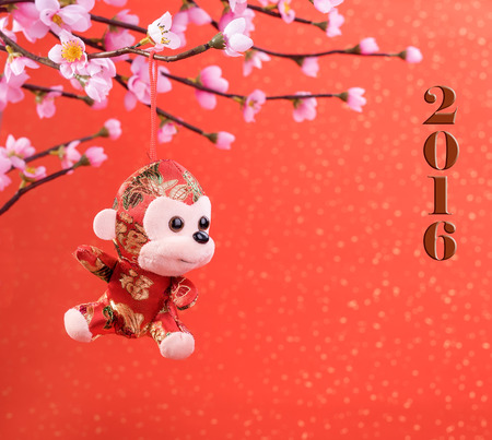 chinese new year: Chinese lunar new year ornaments toy of monkey on festive background Stock Photo