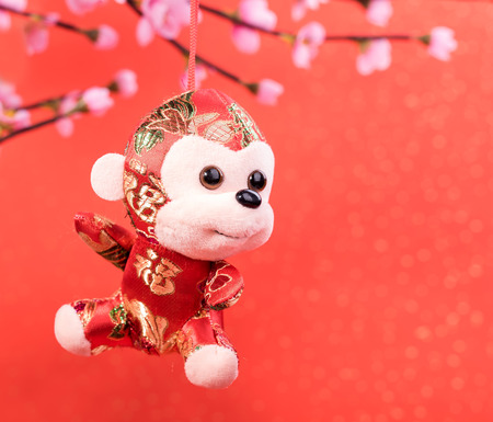 stuffed toys: Chinese lunar new year ornaments toy of monkey on festive background Stock Photo