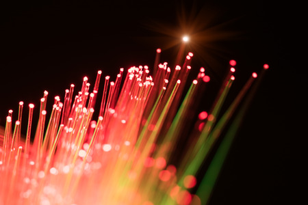 global communication: bunch of optical fibres dinamic flying from deep on technology background, blur
