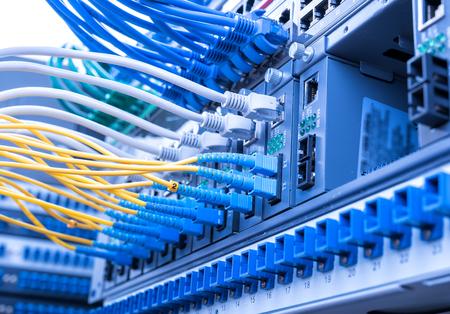 Los cables de fibra óptica conectado a un puerto óptica y cables de red conectados a los puertos Ethernet Foto de archivo