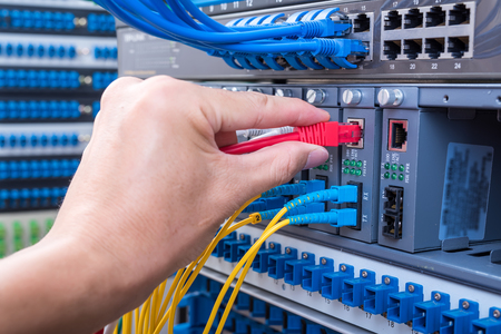 man working in network server room with fiber optic hub for digital communications and internet