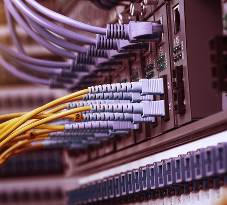 tcp: Fiber Optic cables connected to an optic ports and Network cables connected to ports Stock Photo