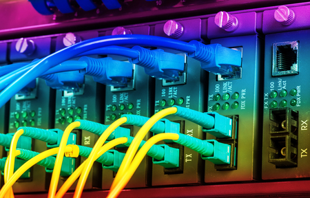 Fiber Optic cables connected to an optic ports and Network cables connected to ports