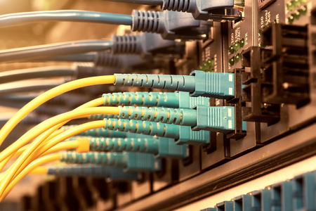 tcp ip: Fiber Optic cables connected to an optic ports and Network cables connected to ports Stock Photo
