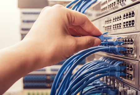 networking cables: man working in network server room with fiber optic hub for digital communications and internet
