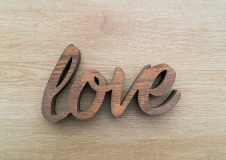 word: Wooden letters forming word LOVE written on wooden background