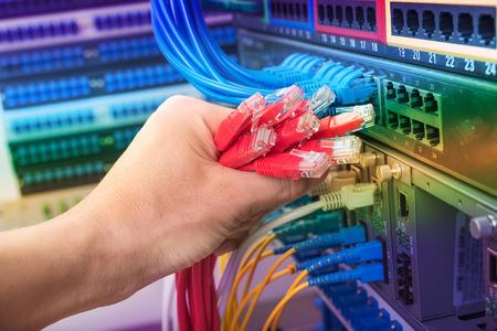 gigabit: man working in network server room with fiber optic hub for digital communications and internet