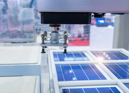 production of solar panels, Industrial robot working in factory,Conveyor Tracking Controller of robotic hand. Stock Photo