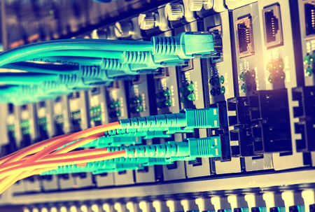 tcp ip: Fiber Optic cables connected to an optic ports and Network cables connected to ports Editorial