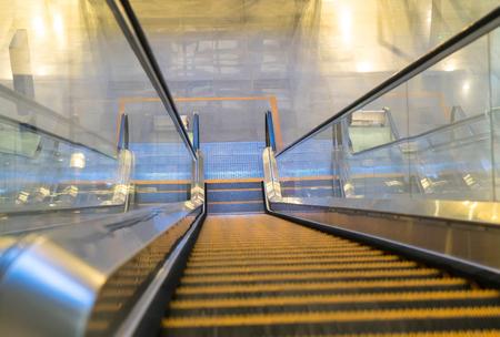 bajando escaleras: Escalera móvil vacía bajando con el desenfoque de movimiento. Foto de archivo